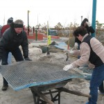 Helpers use wheelbarrows to remove sand